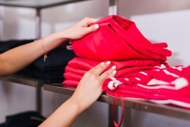 赤いジーンズを保持しているクローズアップの女性