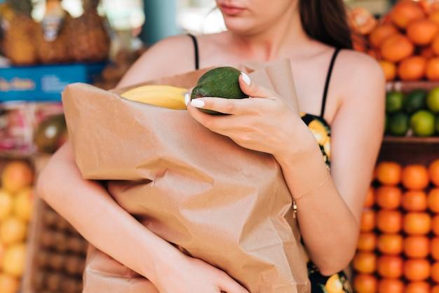 フルペーパーバッグを保持しているクローズアップの女性