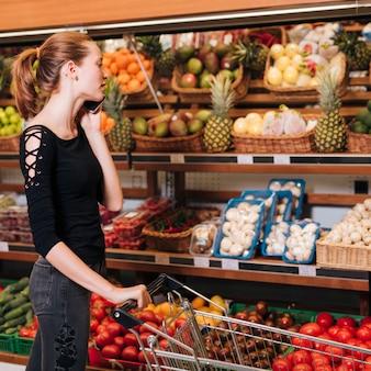 Женщина разговаривает по телефону в продуктовом магазине