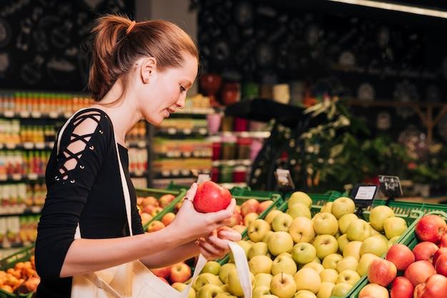 ミディアムショットの女性がリンゴを買う