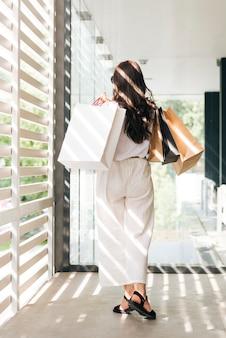 買い物袋を保持している背面のトレンディな女性