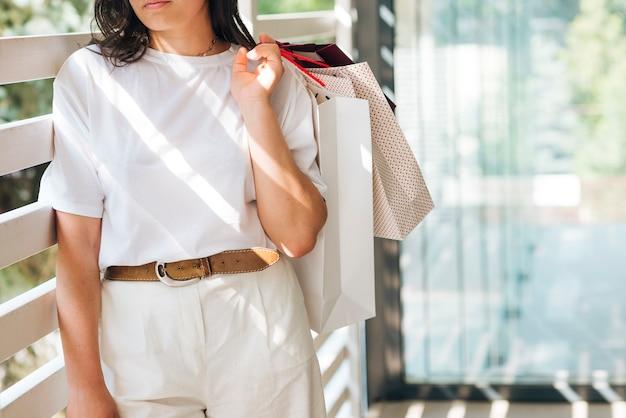 買い物袋を保持しているクローズアップの女性