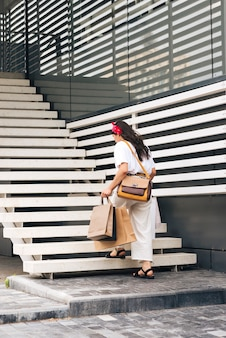 Вид сзади женщина поднимается по лестнице