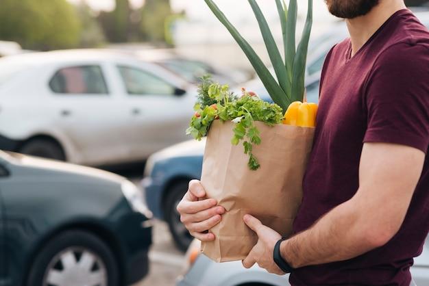 食料品の袋を保持しているクローズアップ男