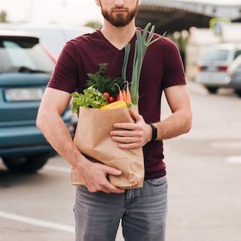 食料品の袋を保持している正面の男