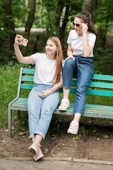 Девушки делают селфи в парке