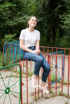 カラフルなフェンスの上に座ってブルネットの少女