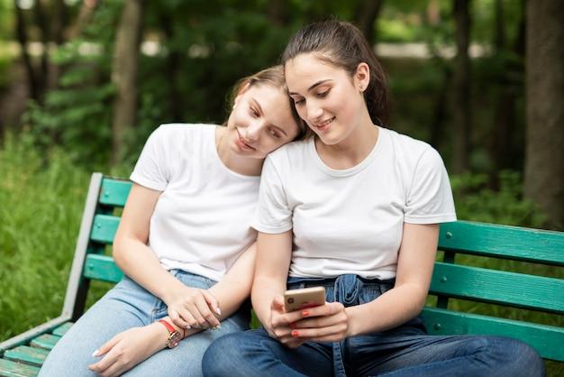 彼女の携帯電話を友達と確認する女の子