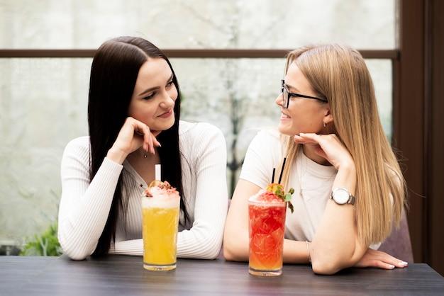Средний снимок красивых друзей, имеющих коктейль
