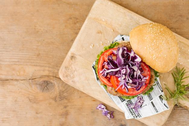 Плоский бургер на деревянной доске