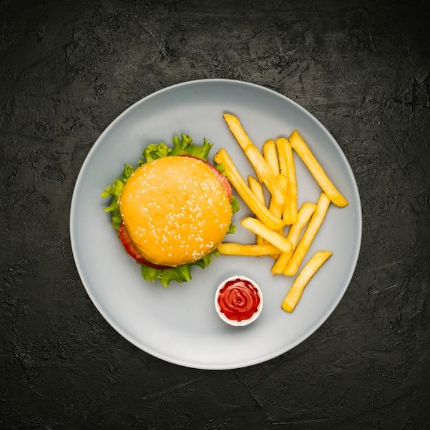 Плоский бургер и картофель фри на тарелке