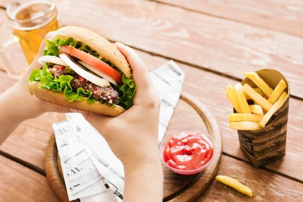 Высокий угол крупным планом руки, держа бургер с гамбургером с картофелем фри