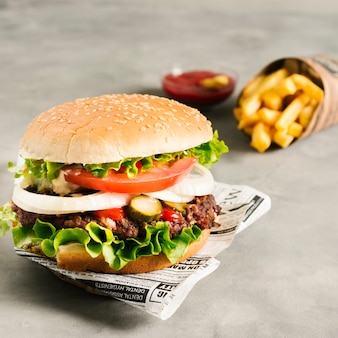 Высокий угол макро бургер с картофелем фри на газете
