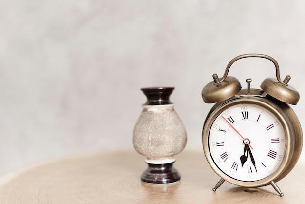 ナイトテーブルの上のクローズアップの古典的な目覚まし時計