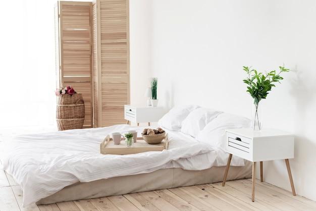 明るい寝室のベッドで朝食付きのトレイ