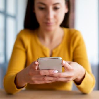 電話で女性のテキストメッセージのミディアムショット