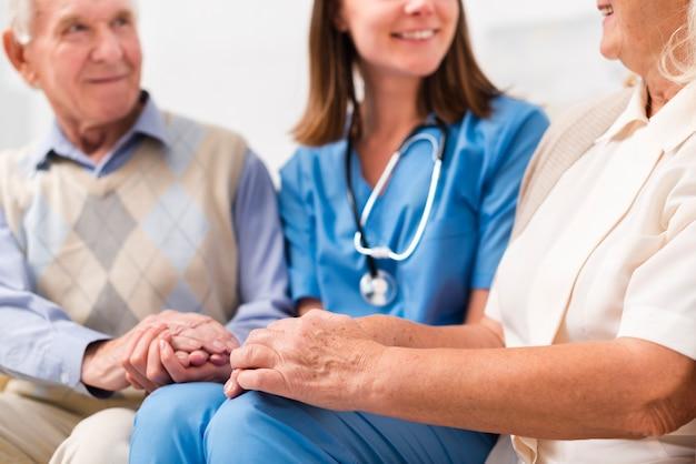 Старик и женщина сидят на желтом диване с медсестрой