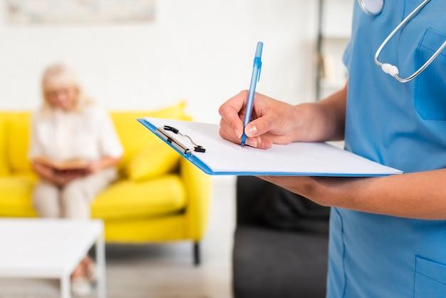 青いクリップボードのクローズアップに書く看護師