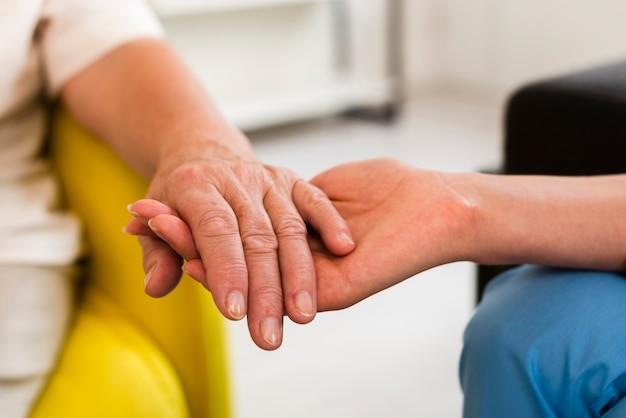 歳の女性とクローズアップ手を繋いでいる看護師