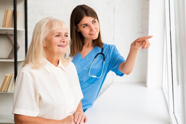 Медсестра среднего роста, указывающая на окно
