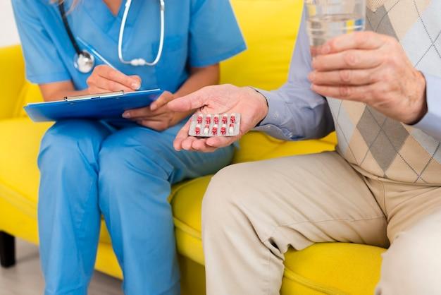 Старик держит свои таблетки