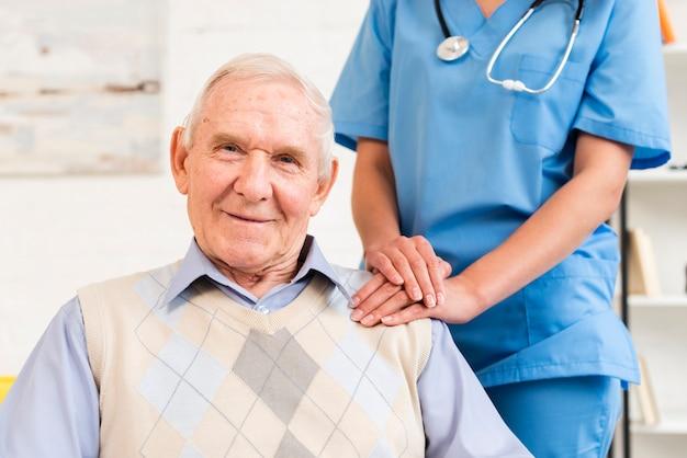 老人の肩を保持している介護者