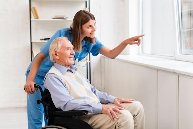 老人と話しながら窓を指している看護師