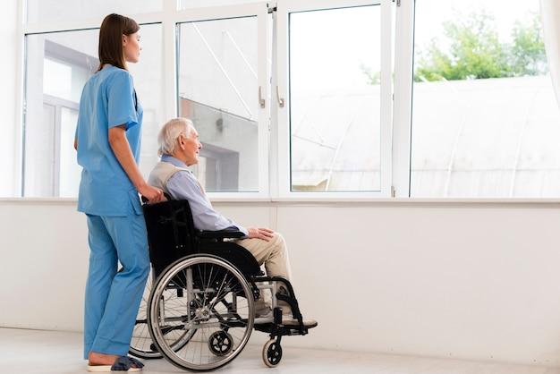 背面ビュー看護師とウィンドウに探している老人