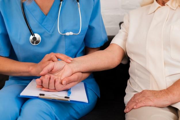 老婦人のクローズアップと手を繋いでいる正面の介護者