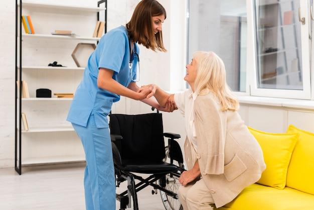 看護師の老婦人の立ち上がりを支援