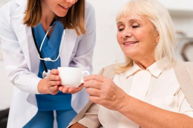 老婦人のクローズアップにお茶を与える看護師