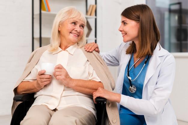 Улыбающаяся пожилая женщина разговаривает с воспитателем