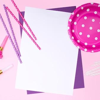 ピンクがかった用品でモックアップする白い誕生日の招待状