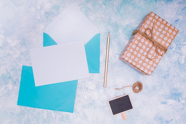 青い封筒と誕生日の招待状をモックアップでフラットレイアウト