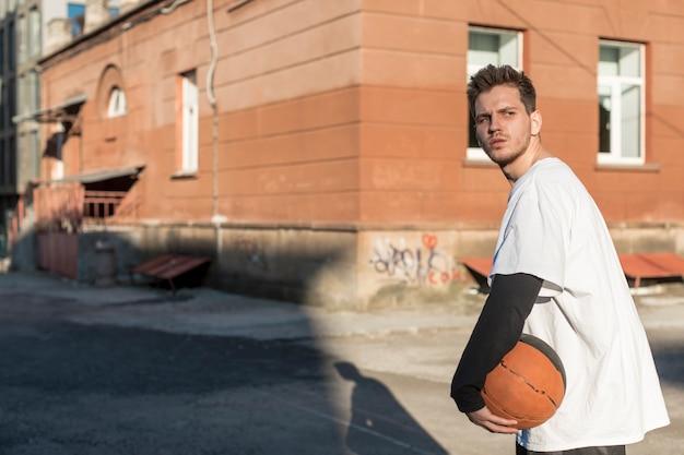 横にバスケットボールを持つ男