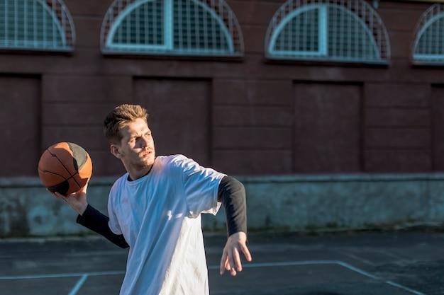 ミディアムショット男、バスケットボールを投げる