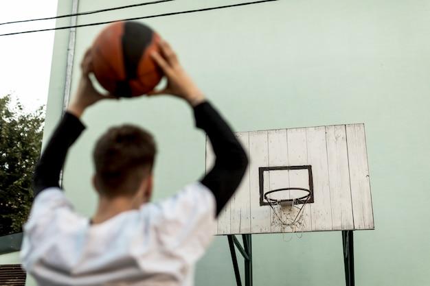 バスケットボールを投げる背面図男
