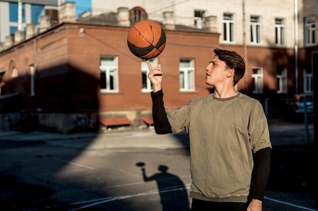 バスケットボール選手が彼の指にボールを回転
