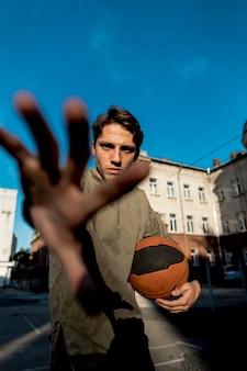 手でカメラを覆っているバスケットボール選手