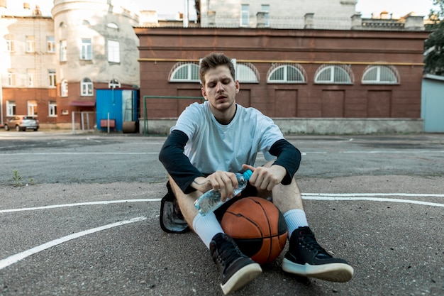Вид спереди сидит человек с баскетболом