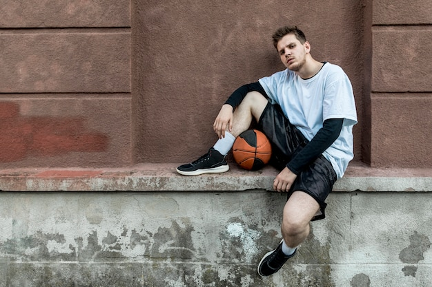 Вид спереди человек расслабляющий с баскетболом