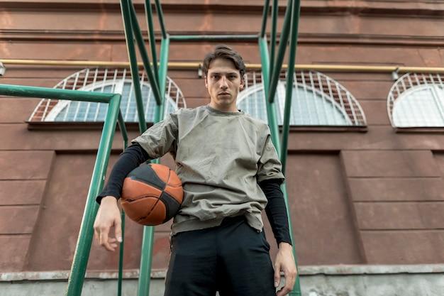 バスケットボールを保持している低ビュー男