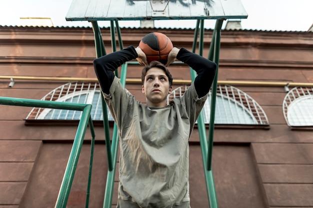 Низкий вид мужчина держит баскетбол