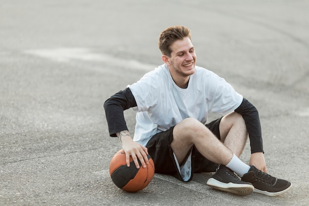 バスケットボールを座っている男