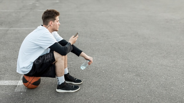 横にあるバスケットボール選手が自分の携帯電話をチェック