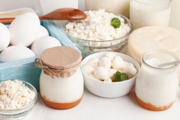 Высокий вид молочных продуктов на белом столе