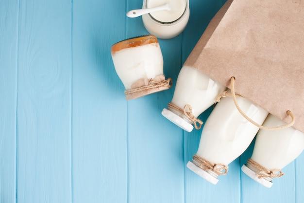 Баночки и бутылки молока в бумажном пакете