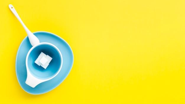 Скопируйте пространства желтый фон с чашкой