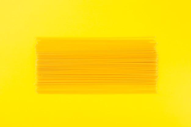 黄色の背景に生のスパゲッティ