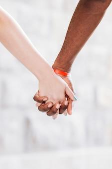 手を繋いでいる異人種間のカップルのクローズアップ